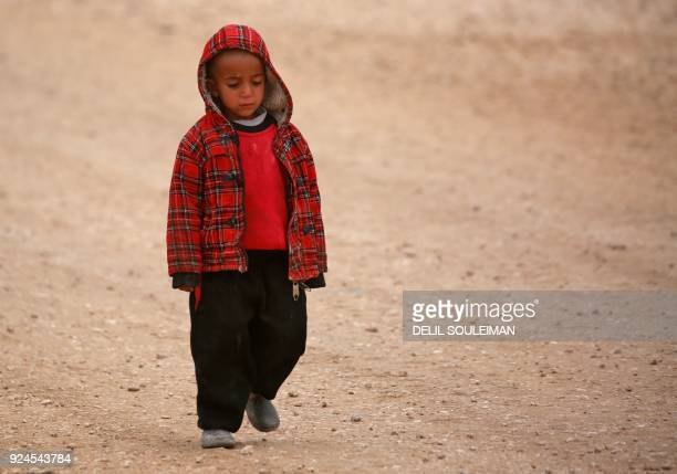 A displaced Syrian child who fled his home in Deir Ezzor city walks in a refugee camp in Syrias northeastern Hassakeh province on February 26 2018 /...