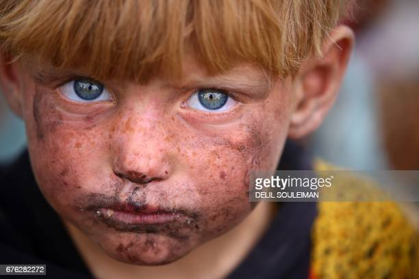 TOPSHOT A displaced Syrian child who fled the countryside surrounding the Islamic State group stronghold of Raqa looks on at a temporary camp in the...