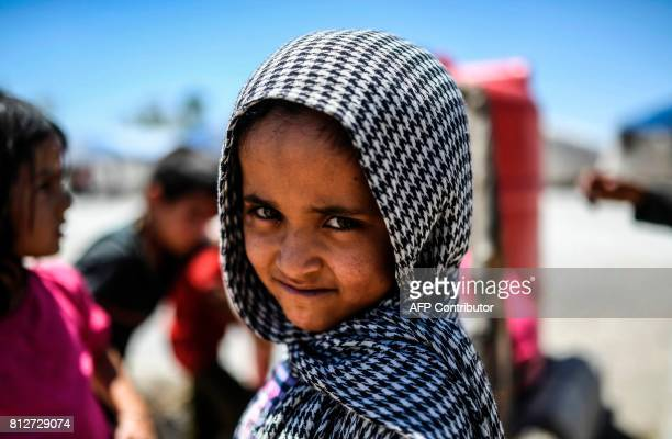 Displaced Syrian child who fled the countryside surrounding the Islamic State group's Syrian stronghold of Raqa, looks on as she waits for water at a...