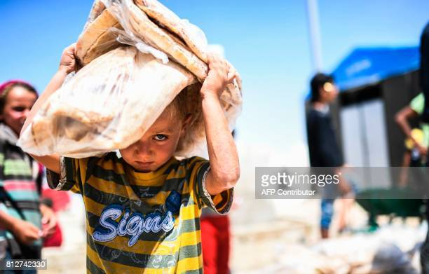 TOPSHOT A displaced Syrian child who fled the countryside surrounding the Islamic State group's Syrian stronghold of Raqa carries bread at a...