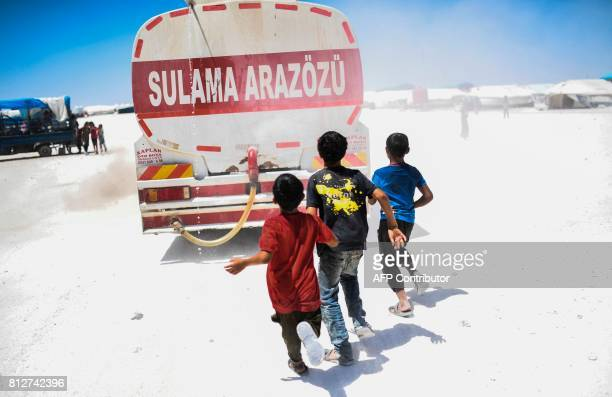 TOPSHOT A displaced Syrian child who fled the countryside surrounding the Islamic State group's Syrian stronghold of Raqa run after a water truck at...