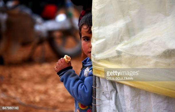Displaced Syrian child, who fled their hometowns due to clashes between regime forces and the Islamic State group, eats outside a tent in Kharufiyah,...