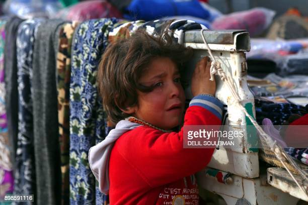 TOPSHOT A displaced Syrian child who was forced to leave his hometown by the war against the Islamic State group is seen at the Ain Issa camp on...
