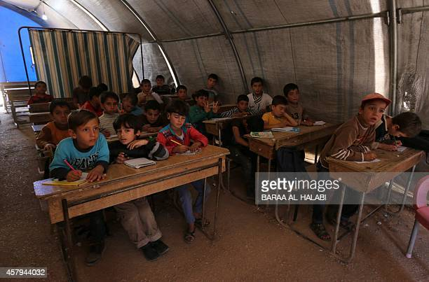 Displaced Syrian children attend a class in the Bab AlSalama camp for people fleeing the violence in the Syria on October 27 2014 on the border with...