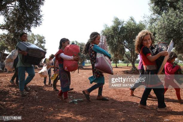 Displaced Syrian children move their belongings to a new spot after sharing a tent with another family in a field near a camp for displaced people at...