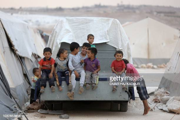 Displaced Syrian children pose for a photograph in the camp 'Hope' in the Syrian village of Kafr Lusein north of the Bab alHawa border crossing on...
