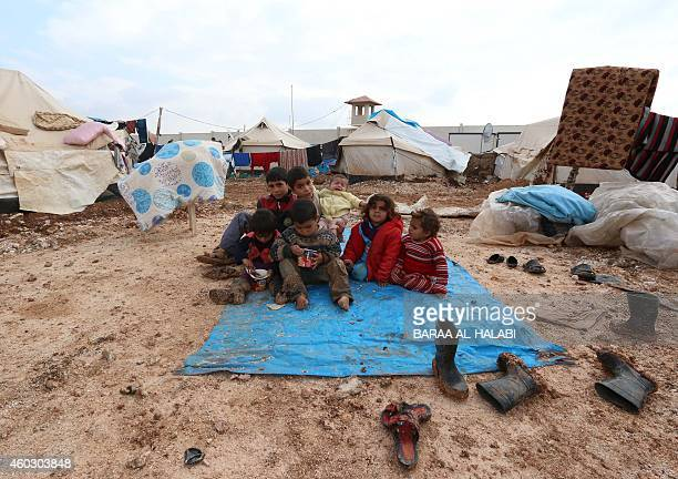 Displaced Syrian children sit on a tarp after heavy rains in the Bab AlSalama camp for people fleeing the violence in Syria on December 11 on the...