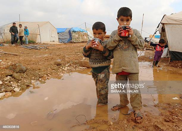 Displaced Syrian children stand in muddy water after heavy rains in the Bab AlSalama camp for people fleeing the violence in Syria on December 11 on...