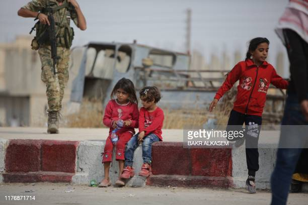 Displaced Syrian children wait as members of Turkey-backed forces distribute aid provided by the Turkish Red Crescent, on October 19 in the Syrian...