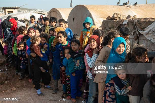 Displaced Syrian children wait in queue to receive humanitarian aid supplied by Humanitarian Relief Foundation's on February 20, 2020 in Idlib,...