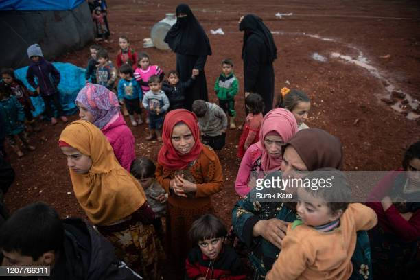 Displaced Syrian children wait to receive humanitarian aid supplied by Humanitarian Relief Foundation's at Marabune camp on February 21, 2020 in...