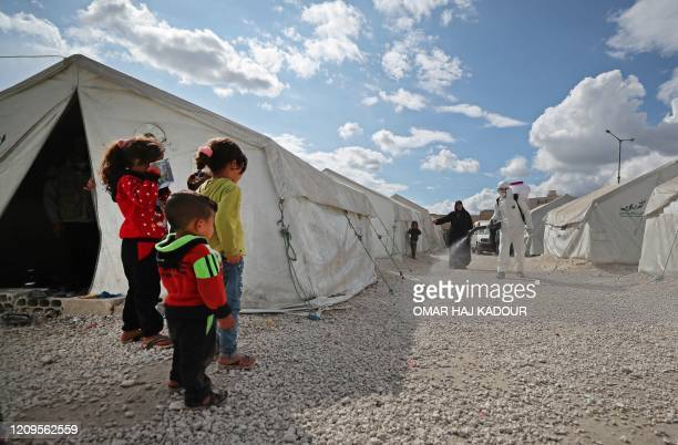TOPSHOT Displaced Syrian children watch as a sanitation worker disinfects their camp next to the Idlib municipal stadium in the northwestern Syrian...