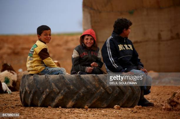 Displaced Syrian children, who fled their hometowns due to clashes between regime forces and the Islamic State group, sit on a wheel outside a tent...