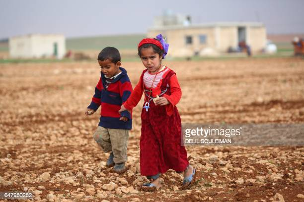 Displaced Syrian children, who fled their hometowns due to clashes between regime forces and the Islamic State group, walk in a field in Kharufiyah,...