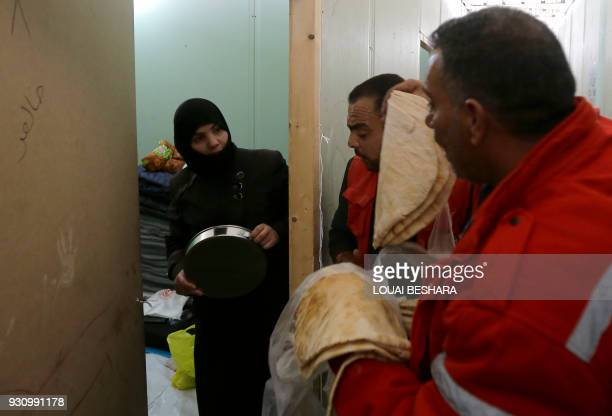 Displaced Syrian civilians received food at a governmentrun shelter after they were evacuated by the army from areas in the Eastern Ghouta region...