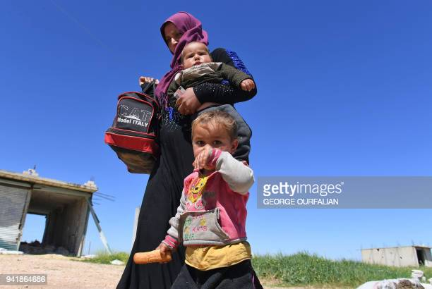 Displaced Syrian families arrive at a checkpoint at the Abu alDuhur crossing to return from rebelheld areas in Syria's northern Idlib province to...