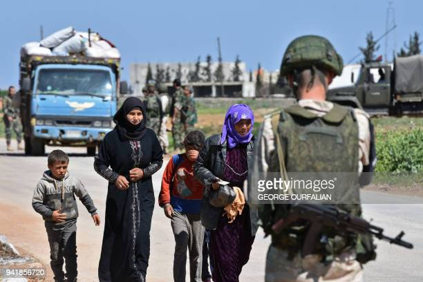 TOPSHOT Displaced Syrian families arrive at a checkpoint manned by Russian forces allied with the Syrian regime at the Abu alDuhur crossing as they...
