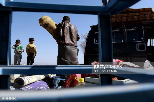 TOPSHOT A displaced Syrian family unload their belongings at a makeshift camp for displaced people near the town of Manbij on March 6 2017 Tens of...