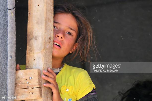A displaced Syrian girl from Daraa stands in a makeshift camp in Quneitra southwestern Syria near the border with Israel on June 22 2018 Thousands of...