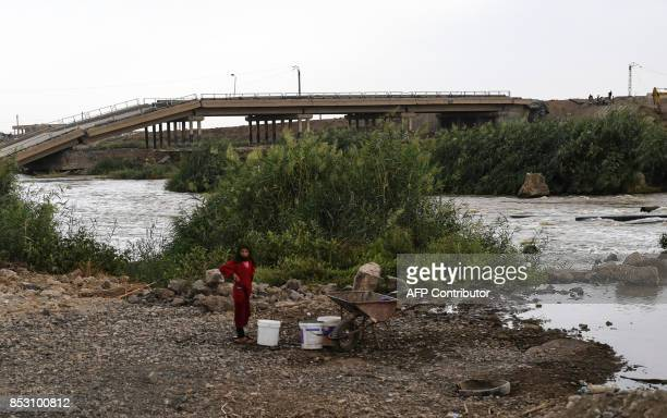 A displaced Syrian girl from Deir Ezzor stands near a river on the outskirts of Raqa on September 24 2017 as Syrian fighters backed by US special...