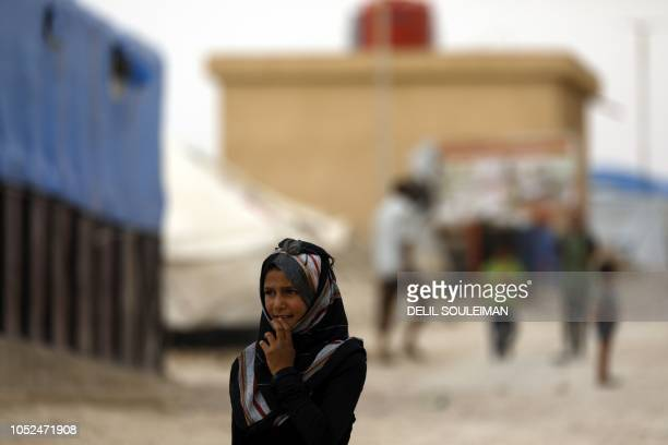 A displaced Syrian girl from the eastern city of Deir Ezzor and Raqa who were forced to leave by the war against the Islamic State group walks around...