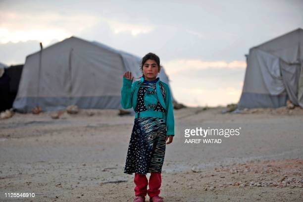 TOPSHOT A displaced Syrian girl waves to the camera at a camp in Kafr Lusin near the border with Turkey in Idlib province in northwestern Syria on...