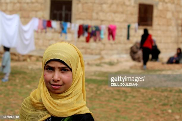 TOPSHOT A displaced Syrian girl who fled their hometowns due to clashes between regime forces and the Islamic State group looks towards the camera in...