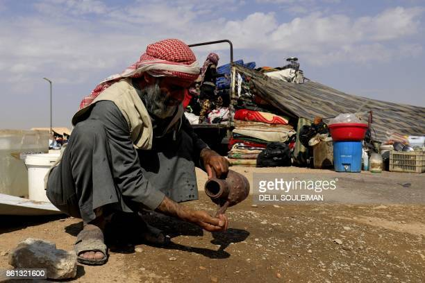 A displaced Syrian man washes his hands at a camp housing people who fled the fighting in Deir Ezzor Mayadeen and Albu Kamal on October 14 in the...
