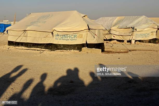 TOPSHOT Displaced Syrian shadows casted on the floor as they watch World Cup soccer match outside Ain Issa camp in Raqqa province on June 17 2018