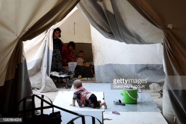 TOPSHOT A displaced Syrian toddler crawls in the camp 'Hope' in the Syrian village of Kafr Lusein north of the Bab alHawa border crossing on...