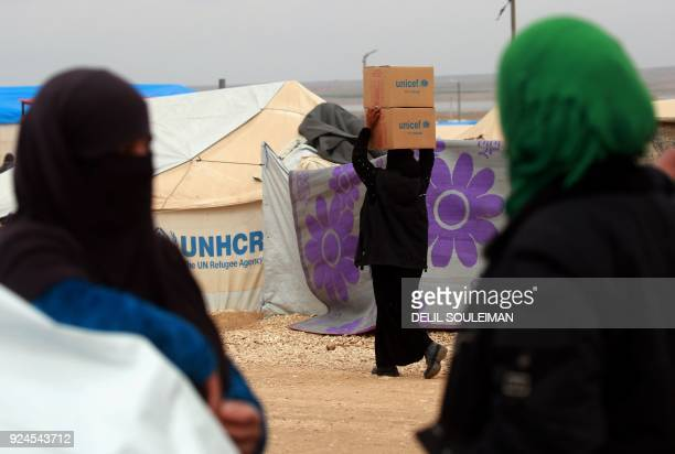 A displaced Syrian who fled her home in Deir Ezzor city carries boxes of humanitarian aid supplied by United Nations Children's Fund at a refugee...