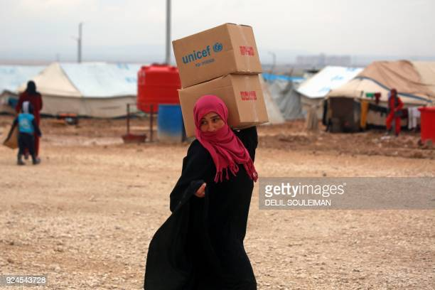 A displaced Syrian who fled her home in Deir Ezzor city carries boxes of humanitarian aid supplied by the United Nations Children's Fund at a refugee...