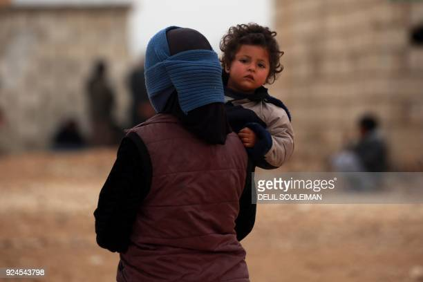 A displaced Syrian who fled her home in Deir Ezzor city carries her child at a refugee camp in Syrias northeastern Hassakeh province on February 26...