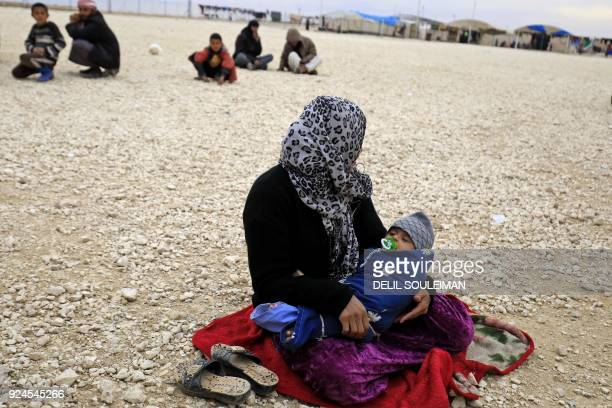 A displaced Syrian who fled her home in Deir Ezzor city sits holding her child at a refugee camp in Syrias northeastern Hassakeh province on February...