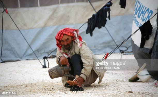 Displaced Syrian, who fled the countryside surrounding the Islamic State group stronghold of Raqa, washes his feet at a temporary camp in the village...