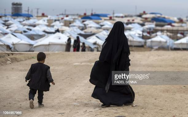 TOPSHOT A displaced Syrian woman and a child walk toward tents at the Internally Displaced Persons camp of alHol in alHasakeh governorate in...