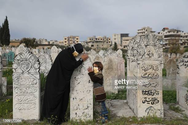 TOPSHOT A displaced Syrian woman and her daughter visits a grave of a relative in the town of Ariha in the northern countryside of Syria's Idlib...