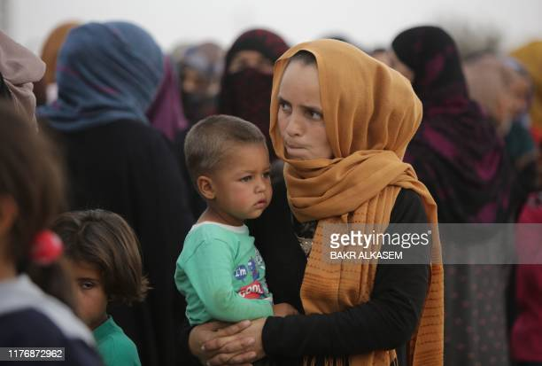 Displaced Syrian woman carries a child as she waits to receive aid provided by the Turkish Red Crescent on October 19 in the Syrian border town of...