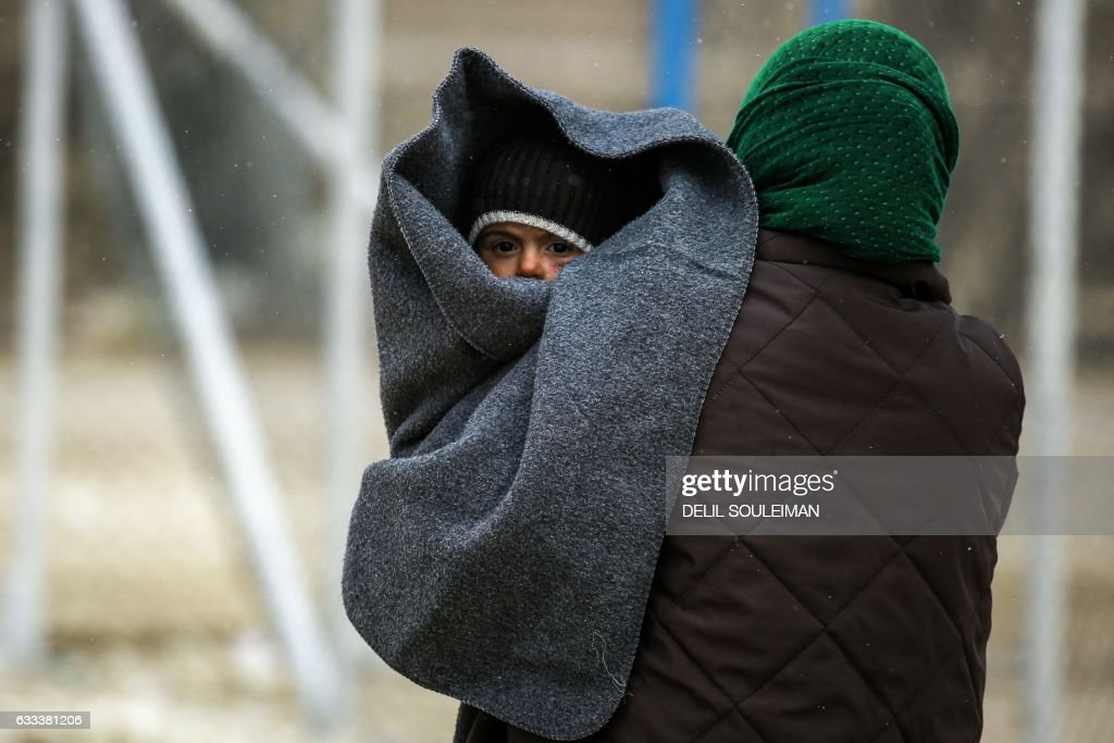 TOPSHOT - A displaced Syrian woman, fleeing from Deir Ezzor city besieged by Islamic State (IS) group fighters, walks through the falling snow carrying a child on her shoulder in a refugee camp in al-Hol, located some 14 kilometers from the Iraqi border in Syrias northeastern Hassakeh province, on February 1, 2017. IS has been fighting fierce battles in Deir Ezzor city, capital of the oil-rich province of the same name which borders Iraq, which the jihadist group has been besieging since early 2015. SOULEIMAN