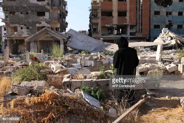 A displaced Syrian woman from Jobar now living in eastern Ghouta visits a grave in a destroyed cemetary in her hometown on the first day of the...