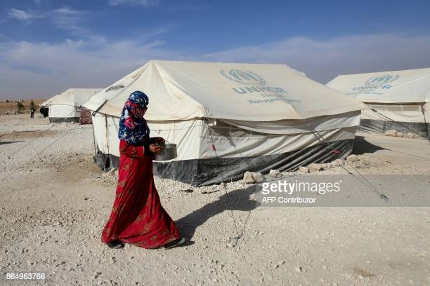 A displaced Syrian woman from Raqa walks at a camp for internally displaced people in Ain Issa on October 21 2017 / AFP PHOTO / Delil souleiman