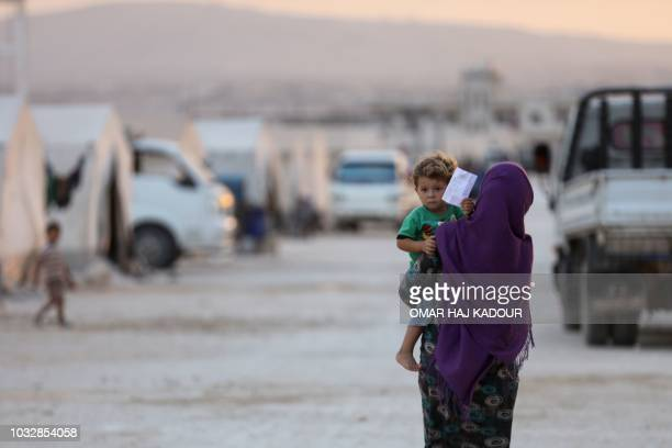 A displaced Syrian woman holds a toddler in the camp 'Hope' in the Syrian village of Kafr Lusein north of the Bab alHawa border crossing on September...