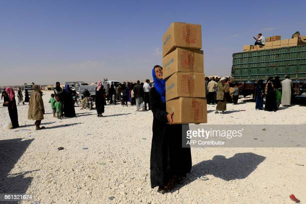 TOPSHOT A displaced Syrian woman reacts as she carries aid parcels at a camp housing people who fled the fighting in Deir Ezzor Mayadeen and Albu...