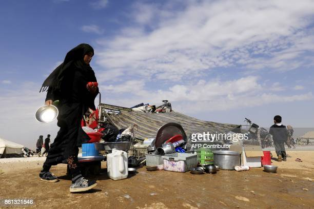 A displaced Syrian woman stands at a camp housing people who fled the fighting in Deir Ezzor Mayadeen and Albu Kamal on October 14 in the town of...