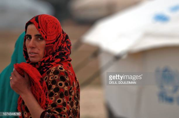 A displaced Syrian woman stands at the Internally Displaced Persons camp of alHol in alHasakeh governorate in northeastern Syria on December 17 2018...