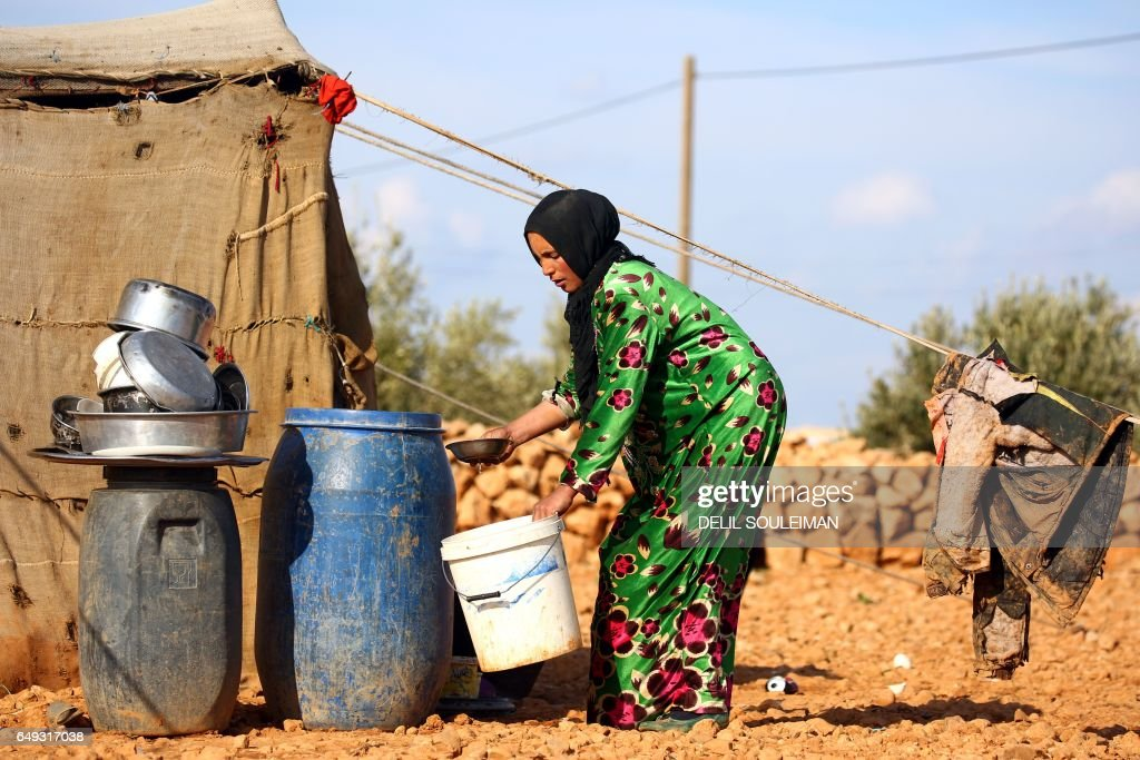 A displaced Syrian woman washes dishes at a makeshift camp in the village of Jab al-Tur (also known as Ukuz Quy) on the southern outskirts of Manbij on March 7, 2017, as the number of people fleeing from the areas of al-Khafsa, Deir Hafer and Maskina rises due to intensified battles between Syrian government forces and Islamic State (IS) group fighters. SOULEIMAN