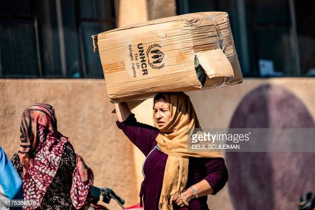 A displaced Syrian woman who fled her home in the border town of Ras alAin receives humanitarian aid on October 12 in the town of Tal Tamr in the...