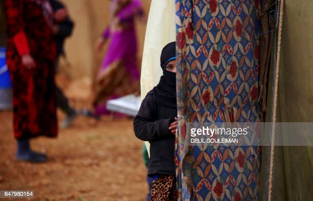 Displaced Syrian woman, who fled her hometown due to clashes between regime forces and the Islamic State group, stands outside a tent in Kharufiyah,...