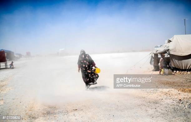 TOPSHOT A displaced Syrian woman who fled the countryside surrounding the Islamic State group stronghold of Raqa walks in the dust at a temporary...