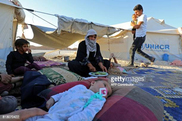 A displaced Syrian woman who fled the countryside surrounding the Islamic State group's Syrian stronghold of Raqa prepares food for her family at a...